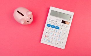 Piggy bank and calculator on color background, top view.